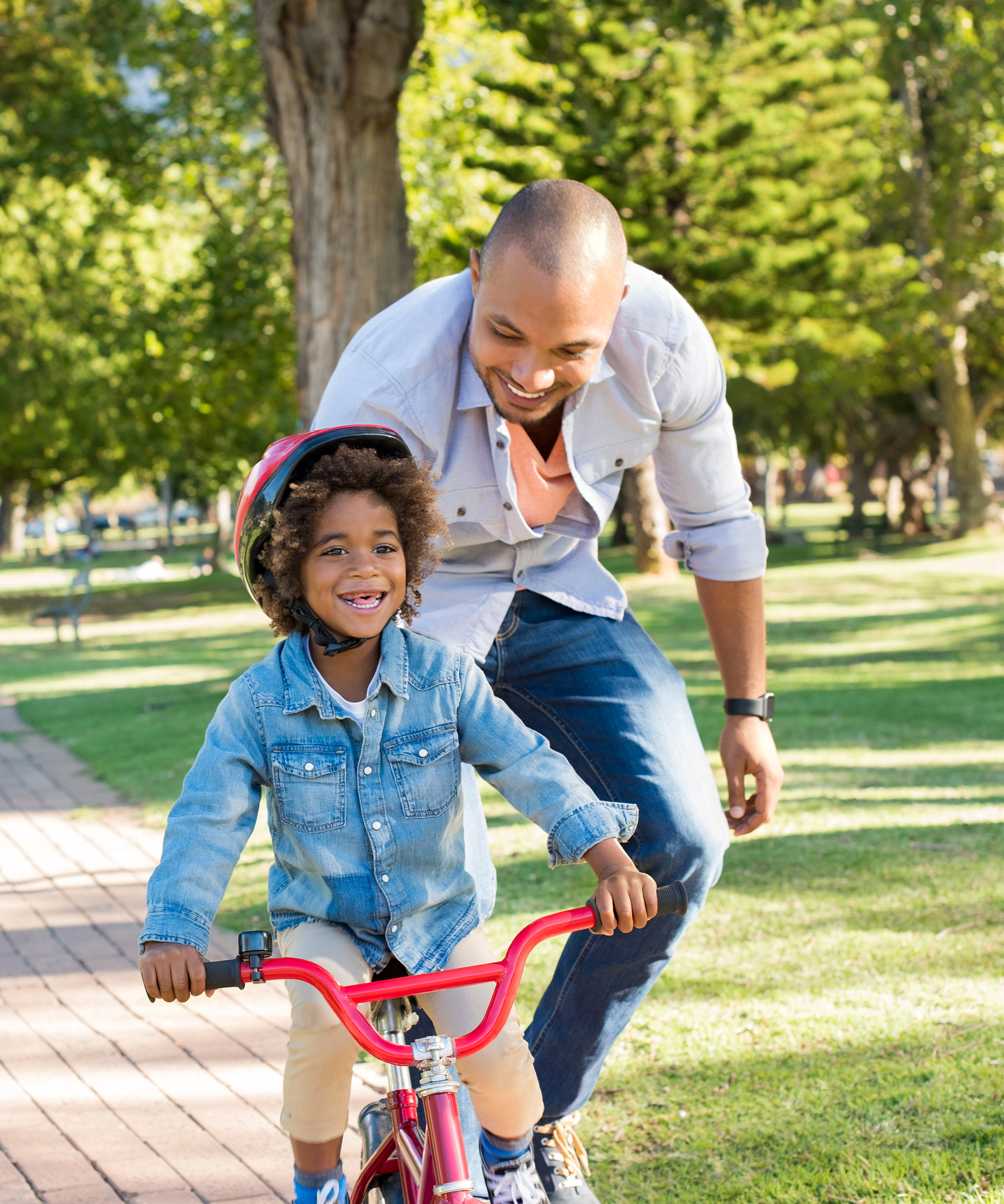 crop-iStock-691524104_super_father teaches child to ride bike_family_diverse